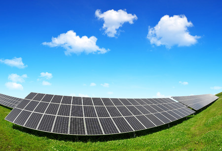 energy costs: Solar panels against blue sky with clouds Stock Photo