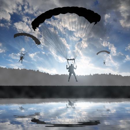 airborne: Silhouette skydiver parachutist landing at sunset