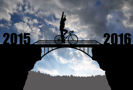 Cyclist riding across the bridge at sunset. Forward to the New Year 2016 Standard-Bild