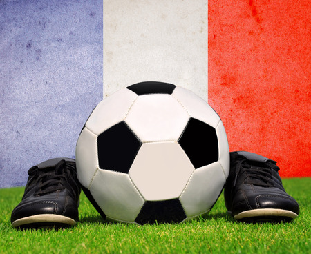 cleats: soccer ball and cleats in grass in the background French flag Stock Photo