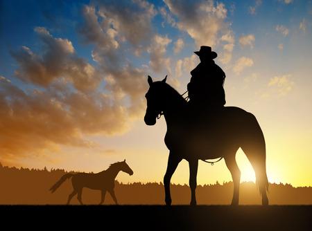 馬と夕日にシルエット カウボーイ