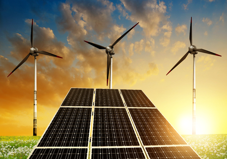 los paneles solares de energía y turbinas de viento en la puesta del sol Foto de archivo