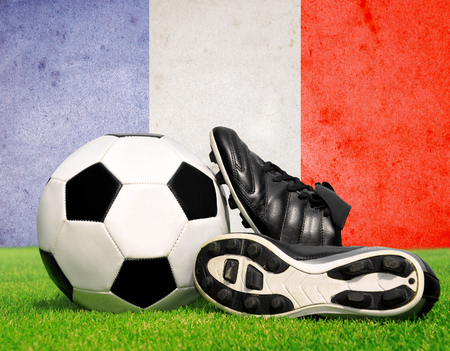 soccer cleats: soccer ball and cleats in grass in the background French flag Stock Photo