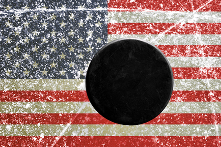 wintrily: Black hockey puck on ice rink with flag of the United States