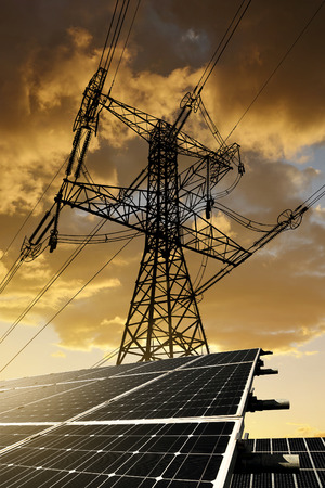Solar panels with electricity pylon at sunset. Clean energy concept. Stockfoto