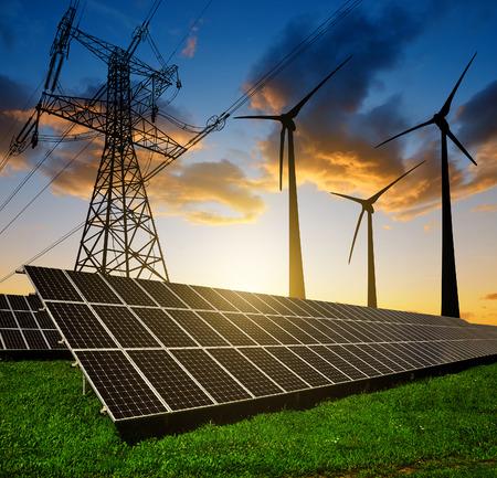 Zonnepanelen met windturbines en elektriciteit pyloon bij zonsondergang. Schone energie concept.
