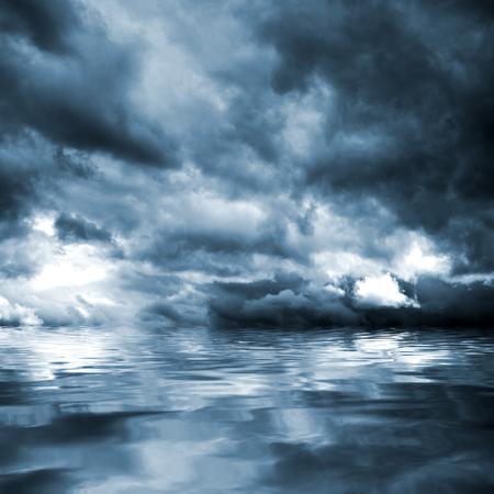 水のレベルの上の雨の前に暗い嵐の雲。自然な背景。