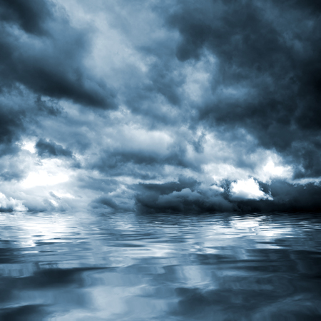 Dark storm clouds before rain above the water level. Natural background.
