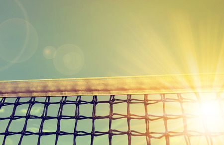 court: Tennis net with sunset sky in the background