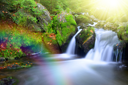 spruit: Waterfall on a mountain creek with rainbow. National park Sumava-Czech Republic