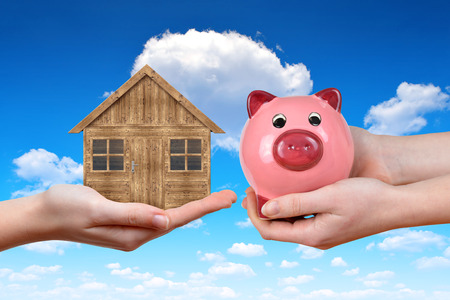 estate: Hands holding wooden house and pink piggy bank. Concept of saving for housing