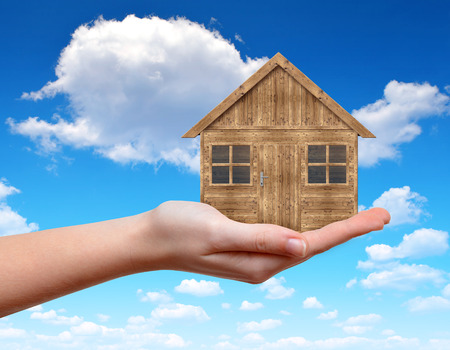 home loan: Wooden house in hand on the background blue sky Stock Photo