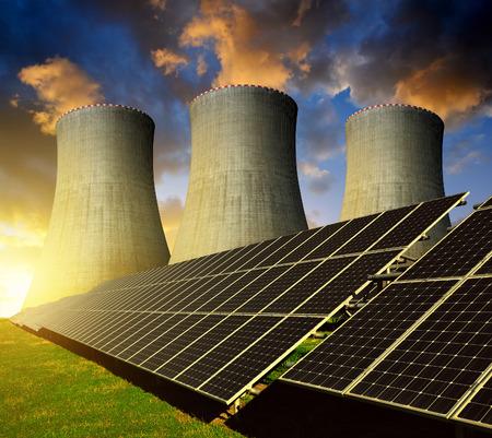 energia solar: paneles de energía solar y planta de energía nuclear en la puesta del sol.