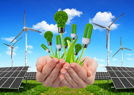 energías renovables: Mano que sostiene bombillas ecológicas. En el fondo los paneles de energía solar y turbinas eólicas. Concepto de energía limpia.