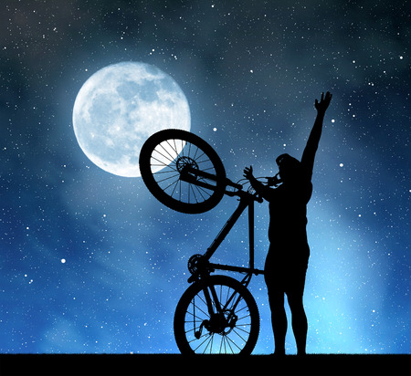 man in the moon: Silhouette of a man with a bicycle in the night sky with the moon.