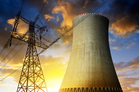 Nuclear power plant with high voltage towers against the sunset