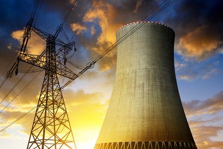 Kerncentrale met een hoog voltage torens tegen de zonsondergang
