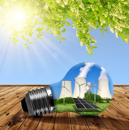 saving energy: Nuclear power plant with solar panel and wind turbines in lightbulb. Energy resources concept. Stock Photo