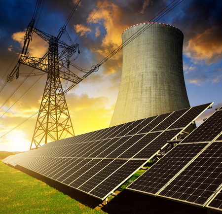 solar power plant: Solar energy panels, nuclear power plant and electricity pylon at sunset Stock Photo