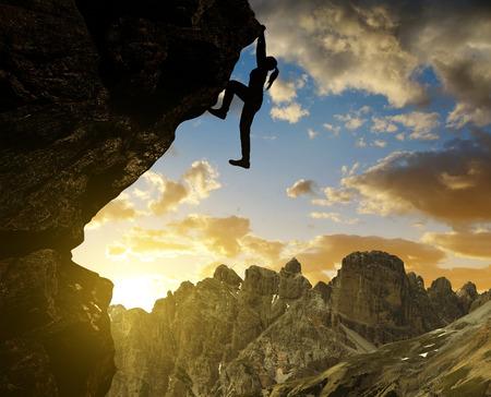 escalando: Silhoutte de la muchacha de escalada en roca en la puesta del sol en los Alpes Dolomitas, Italia Foto de archivo