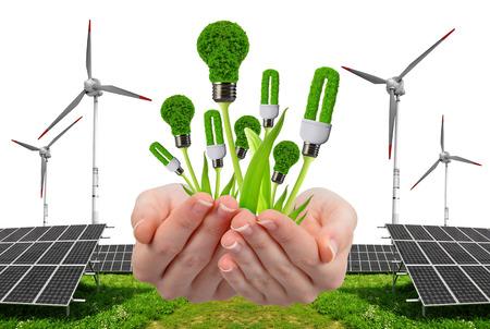 ahorro energia: Mano que sostiene bombillas ecológicas. En el fondo los paneles de energía solar y turbinas eólicas. Concepto de energía limpia.