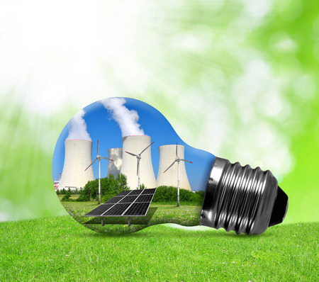 power plant: Nuclear power plant with solar panel and wind turbines in lightbulb . Energy resources concept. Stock Photo