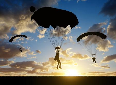 parachutist: Silhouette skydiver parachutist landing at sunset