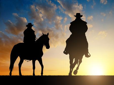 silueta ciclista: Silueta del vaquero con el caballo en la puesta del sol Foto de archivo