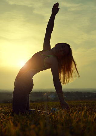 woman stretching: Silhouette of young woman stretching on a meadow at sunset