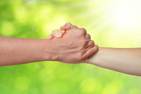 business relationship: Handshake of friendship on green natural background