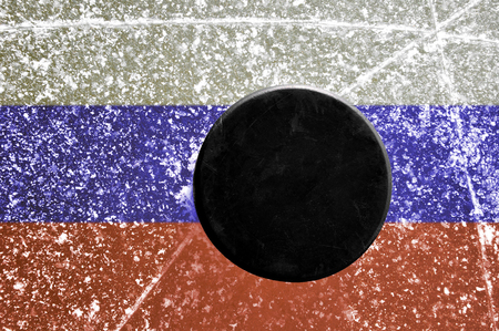 wintrily: Black hockey puck on ice rink with Russian flag.