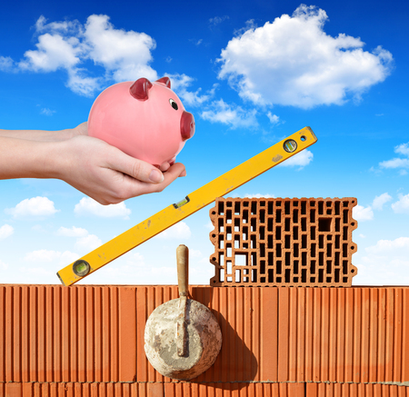 masonry: Masonry tools on a brick wall and a hand holding a piggy bank. Concept savings to build a new house. Stock Photo