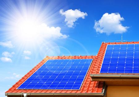 energy saving: El panel solar en el techo de la casa en el fondo del cielo soleado.