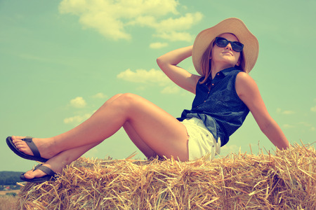 straws: Woman with hat on a bale of straw