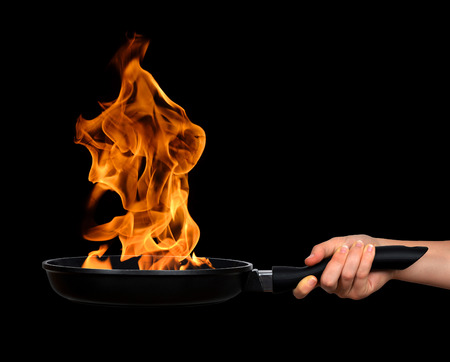 Woman's hand holding a frying pan with flames on black background Archivio Fotografico
