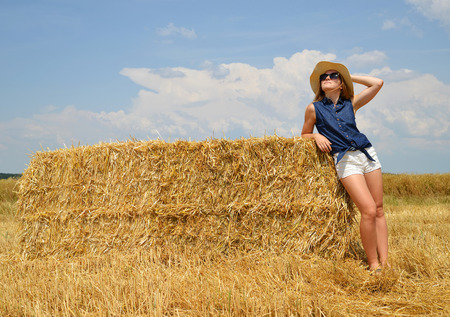 bale: Woman with hat resting on a bale of straw on the field Stock Photo