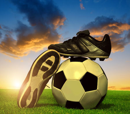 soccer cleats: Soccer ball and shoes in grass at sunset