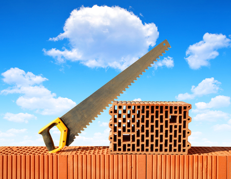 redbrick: Brick wall with handsaw on bricks. Bricklaying work.