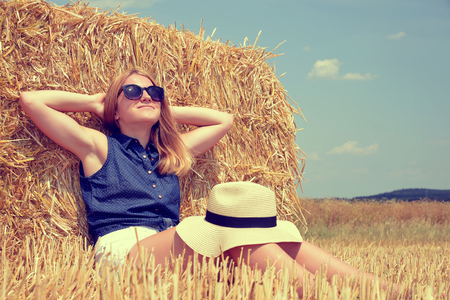 Woman resting on a bale of straw on the field Stock Photo
