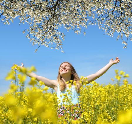 jovenes felices: Joven mujer feliz en campo floreciente de colza en primavera Foto de archivo