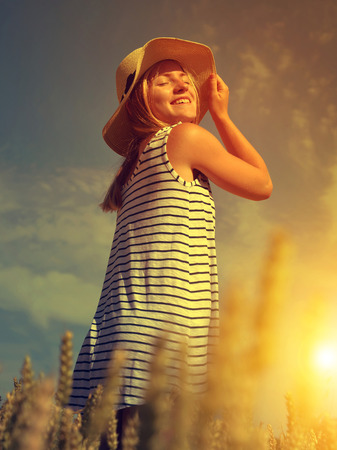 woman sunset: Woman with hat in wheat field at sunset. Stock Photo