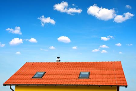 Maison de toit avec toit de tuiles sur le ciel bleu.