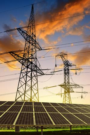 torres de alta tension: Los paneles solares con torres de energía al atardecer. Concepto de energía limpia.