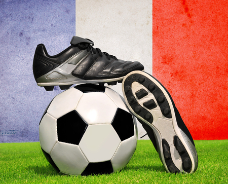 cleats: Soccer ball and cleats in grass in the background French flag