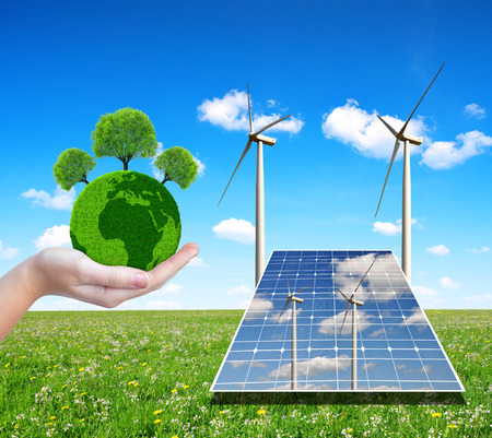 silicium: Solar energy panels with wind turbines and green planet in hand. Concept of environmental protection. Stock Photo