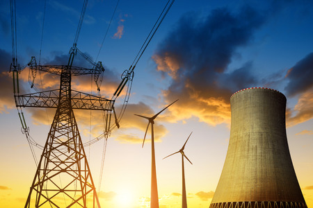 nuclear reactor: Nuclear power plant with wind turbines and electricity pylon in the sunset. Energy resources concept. Stock Photo