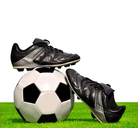 football cleats: Soccer ball and shoes in grass on white background