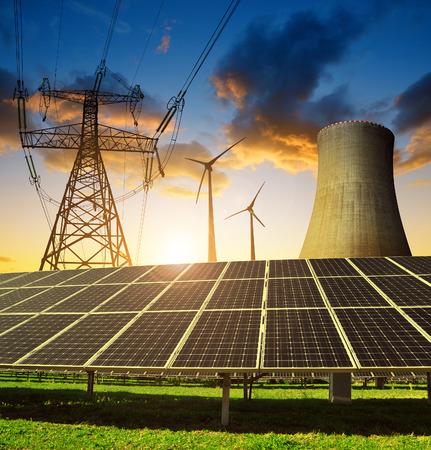 radiacion solar: Los paneles solares en la planta de energía nuclear de fondo, turbinas de viento y torre de alta tensión al ponerse el sol. Concepto de los recursos energéticos.