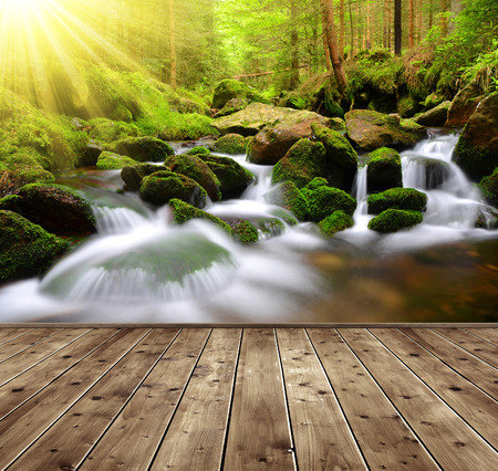 spruit: Waterfall on a mountain creek in the foreground a wooden planks. Stock Photo