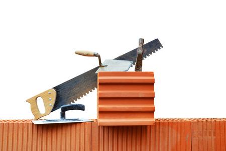 Masonry tools on a brick wall. Bricklaying work.
